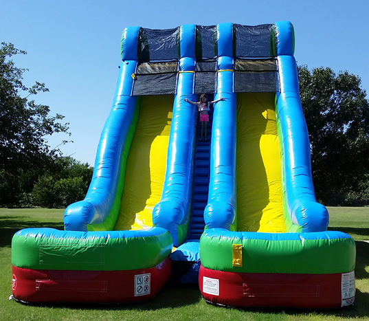 More height. More lanes. More fun! Our 24' Brilliant Blue Double Lane Water Slide is perfect for any party or get together! Race to the splash zone! This slide can be used as a water slide or, turn off the water and it's now dry! All our wet and dry slides have an inflated landing zone for safe use both wet and dry. All our water slides have triple thread seams with an additional glue seam for an optimum seal, to eliminate water from seeping inside. This seal also keeps dirt and sand from damaging the seams which prolongs the life of the slide and play time. The climbing area, top launch platform, and entrance area feature a non slip grip material for a safer experience and peace of mind when used as a water slide. Our wet and dry slides feature a built in misting system, set it and forget it! The splash zone has built in drains on both sides to keep the water level ideal for all ages.